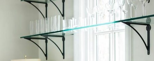 photo showing glasses arranged on top of a glass shelf