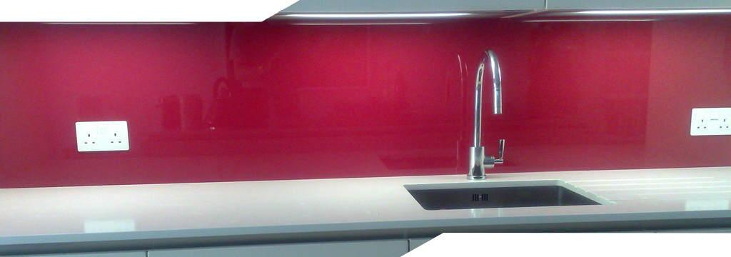 wide angled shot of a pink coloured glass splashback fitted in a kitchen