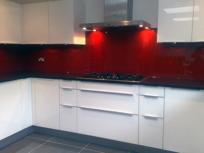 Red glass wall panel fitted behind hob.